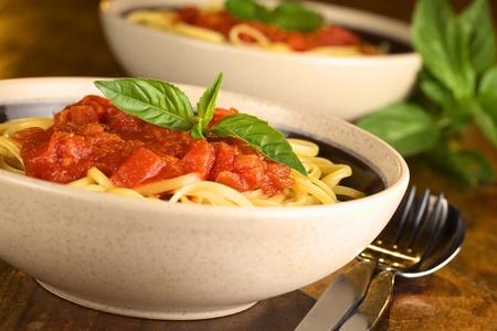 Spaghetti à la sauce tomate garni d'une feuille de basilic frais servi dans un bol une Focus sélective, Concentrez-vous sur la feuille de basilic à l'avant Banque d'images