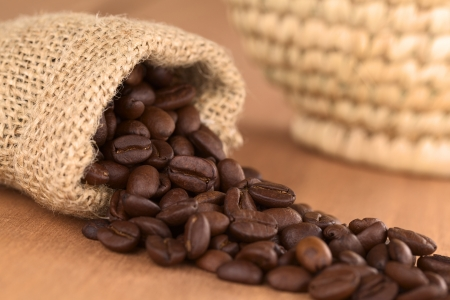 Roasted coffee beans in jute bag on wood with woven basket in the back  Selective Focus, Focus on the coffee beans turned to the front in the middle of the image Stock Photo - 13618997