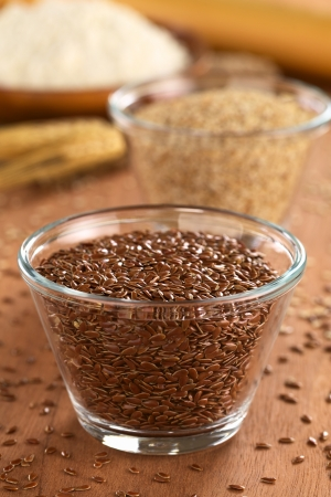 Brown flax seeds in glass bowl with sesame and flour in the back (Selective Focus, Focus one fourth into the seeds in the bowl) photo