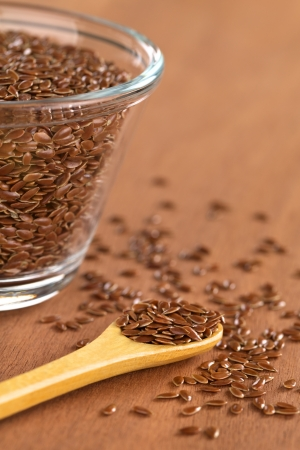 Brown flax seeds on wooden spoon with glass bowl on the side (Selective Focus, Focus on the front flax seeds on the spoon) Stock Photo - 13649997