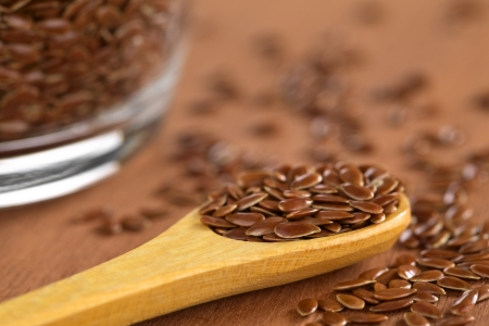 flaxseed: Brown flax seeds on wooden spoon with glass bowl on the side (Selective Focus, Focus on the front flax seeds on the spoon)