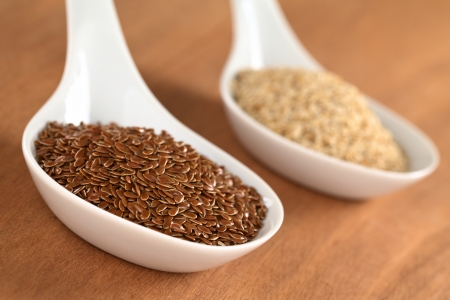 Brown flax seeds and sesame on ceramic spoon (Selective Focus, Focus on third into the flax seeds) photo