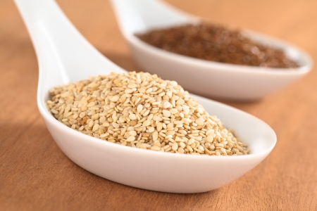 flaxseed: Sesame seeds and brown flax seeds on ceramic spoon (Selective Focus, Focus one third into the sesame seeds)