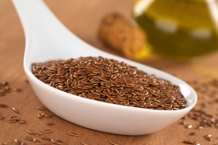 Brown flax seeds on ceramic spoon with linseed oil in the back (Selective Focus, Focus on third into the flax seeds on the spoon) Stock Photo - 13649857