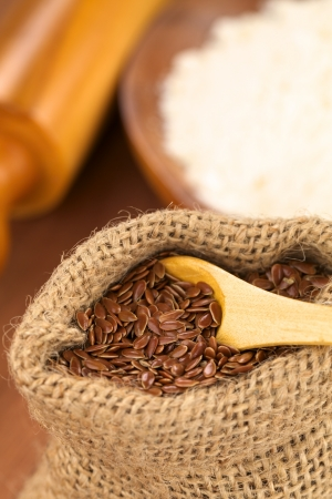 Brown flax seeds in jute bag with flour and rolling pin in the back (Selective Focus, Focus on the front flax seeds on the wooden spoon) photo