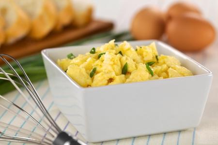 huevos revueltos: Huevos revueltos con cebolla en un bol con batidor en el lado (Enfoque diferencial, foco de un tercio a la taza)