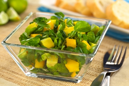 Fresh watercress, mango and avocado salad in glass bowl with fork and knife on the side and bread in the back (Selective Focus, Focus on the mango and avocado pieces in the front)