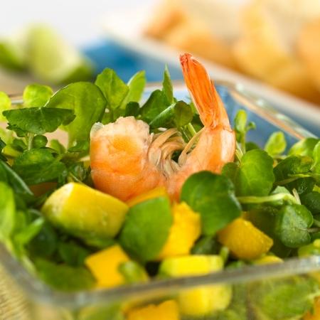 berros: Camarón en el berro fresco, ensalada de mango y aguacate en un tazón de vidrio con barra de pan en el fondo (enfoque selectivo, foco en el camarón)