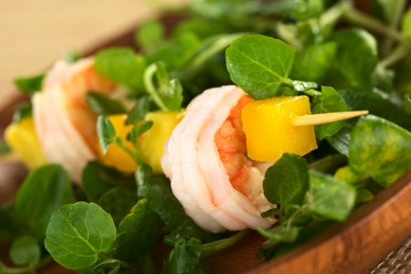 prawn skewers: Fresh cooked shrimp, mango and avocado on skewer with watercress leaves on wooden plate (Selective Focus, Focus on the front rim of the shrimp) Stock Photo