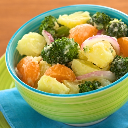 broccoli salad: Green bowl full of fresh salad of potato, broccoli, mandarin and onion with mayonnaise (Selective Focus, Focus on the broccoli and the potato in the middle of the bowl)
