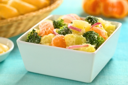 broccoli salad: Bowl full of fresh salad of potato, broccoli, mandarin and onion with mayonnaise (Selective Focus, Focus on the mandarin, broccoli and the potato in the front) Stock Photo