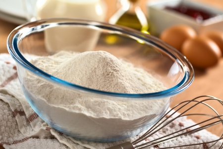 Preparing a dough for crepes or pancakes with wheat flour in glass bowl, milk, eggs and oil in the back and a beater Stock Photo - 13765229
