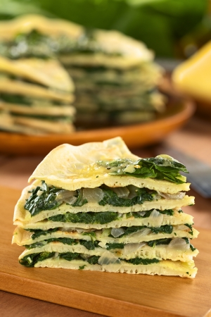 A piece of fresh homemade savory crepes layered with chard (mangold) and onion with cheese on top on wooden board (Selective Focus, Focus on the front of the piece)  Stock Photo - 13765330