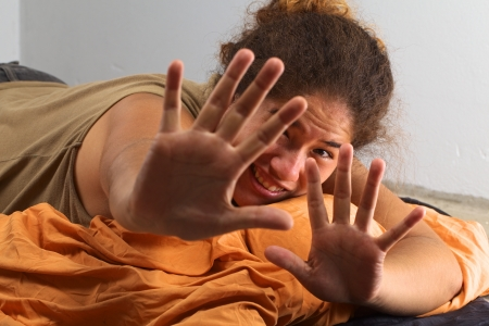 squatter: Young Peruvian woman lying on a sleeping bag on the floor doesnt want to be photographed (Selective Focus, Focus on the face of the woman) Stock Photo