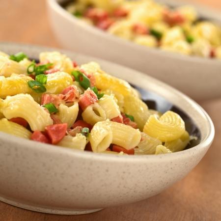 macarrones: Dos copas llenas de pasta fresca hecha en casa macarrones con piezas de salchicha, queso rallado y la cebolla verde (Enfoque diferencial, foco de un tercio en el primer plato)