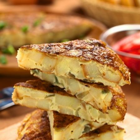 Frais maison espagnole tortilla (omelette aux pommes de terre et oignons) tranches (sélective focus, Concentrez-vous sur le bord avant de la tranche supérieure tortilla supérieure)