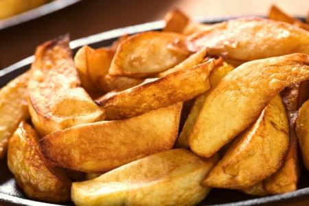 Pâtes fraîches croustillantes coins pommes de terre frites sur la plaque métallique (Mise au point sélective, Focus tiers dans les pommes de terre) Banque d'images