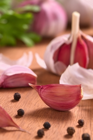 Garlic cloves with black pepper corns on wooden surface (Selective Focus, Focus on the front of the garlic clove on the right)