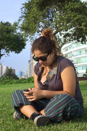 Beautiful young Peruvian woman text messaging on mobile phone in park (Selective Focus, Focus on the face and the hands of the woman) photo