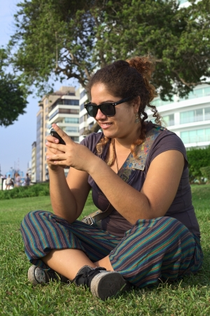 Beautiful smiling young Peruvian woman text messaging on mobile phone in park (Selective Focus, Focus on the face of the woman) photo