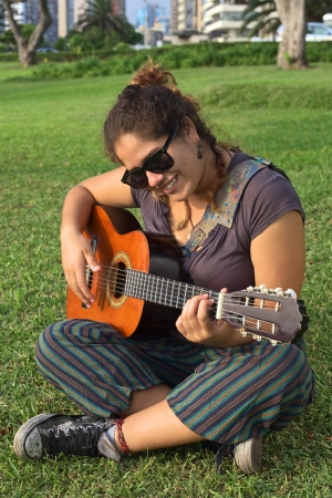 free time: Beautiful smiling young Peruvian woman playing the guitar in a park (Selective Focus, Focus on the face of the woman)