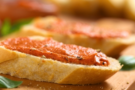 sandwich spread: Homemade tomato-butter spread on baguette slices with fresh ground pepper on wooden board (Selective Focus, Focus on the front of the spread)
