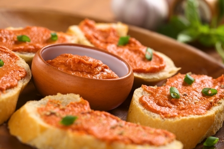 Fresh homemade tomato-butter spread in small bowl with canapes on wooden plate (Selective Focus, Focus on the middle of the spread in the bowl) Stock Photo - 13911588