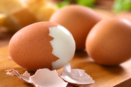 Freschi uova sode con guscio accanto su Focus tavola di legno selettivo, si concentrano sul frontale della calotta del primo uovo