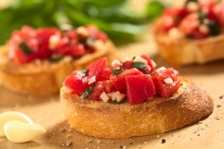 Fresh homemade crispy Italian antipasto called Bruschetta topped with tomato, garlic and basil on wooden board (Selective Focus, Focus on the front of the first bruschetta)