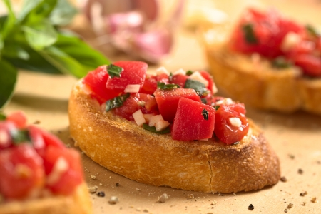 Fresh homemade crispy Italian antipasto called Bruschetta topped with tomato, garlic and basil on wooden board (Selective Focus, Focus on the front of the middle bruschetta)  Stock Photo