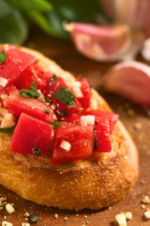 italian cuisine: Fresh homemade crispy Italian antipasto called Bruschetta topped with tomato, garlic and basil on wooden board (Selective Focus, Focus on the tomato piece in the front)