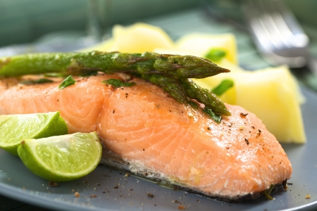 Baked salmon fillet with green asparagus, lime wedges and boiled potatoes (Selective Focus, Focus on the tip of the asparagus heads) photo