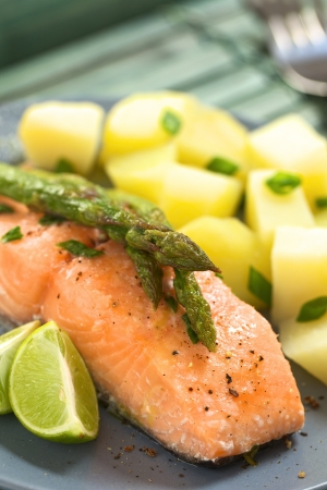 Baked salmon fillet with green asparagus, lime wedges and boiled potatoes  Stock Photo
