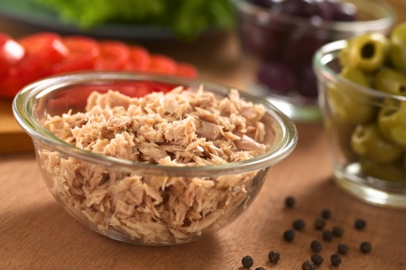 tuna salad: Canned tuna in glass bowl with fresh salad ingredients (olives, tomato, lettuce) in the back