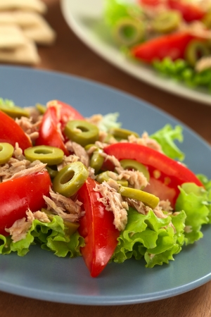Fresh tuna, tomato and green olive salad served on lettuce leaf on blue plate  photo