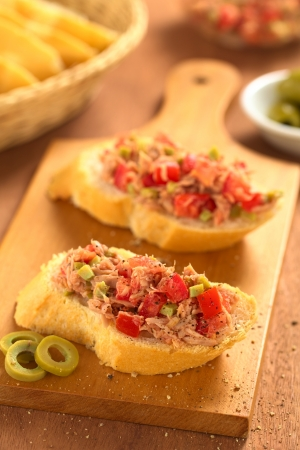 seasoned: Slice of baguette with fresh tuna, green olive and tomato spread seasoned with ground pepper on wooden board (Selective Focus, Focus on the front of the spread on the first bread)