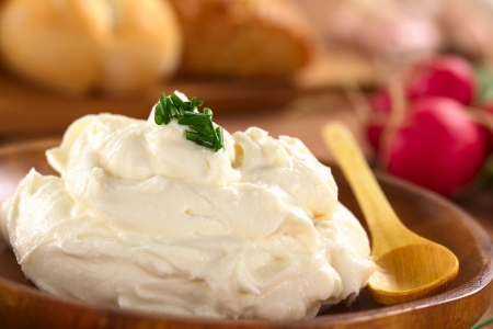 cebollin: Crema de queso fresco extiende sobre la placa de madera con las cebolletas en la parte superior, el r�bano y los bollos en la parte de atr�s (Enfoque, Enfoque en el cebollino en la parte superior de la crema de queso) Foto de archivo