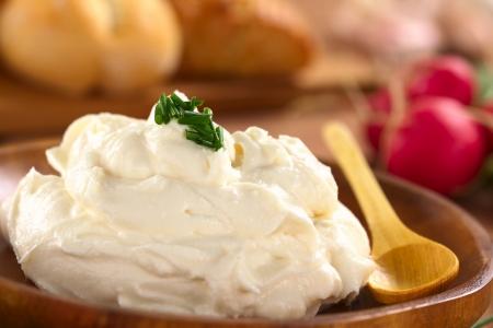 Fromage à la crème fraîche étalée sur plaque de bois avec de la ciboulette sur le dessus, le radis et des petits pains dans le dos (Mise au point sélective, Concentrez-vous sur la ciboulette sur le dessus de fromage à la crème)
