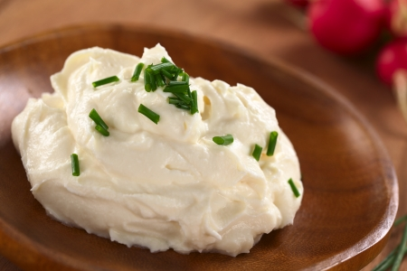 spread: Fresh cream cheese spread on wooden plate with chives on top and radish in the back (Selective Focus, Focus on the chives on the top of the cream cheese)