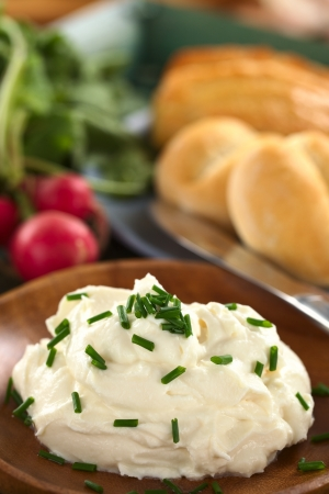 quark: Fresh cream cheese spread on wooden plate with chives on top, radish and buns in the back (Selective Focus, Focus on the chives on the top of the cream cheese)