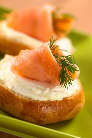 salmon ahumado: Salmón ahumado y queso crema canapés adornados con eneldo (Enfoque, Enfoque en la parte delantera del salmón) Foto de archivo
