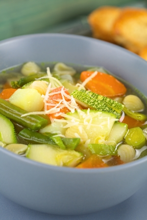 minestrone: Bowl full of fresh homemade vegetarian Italian minestrone soup made of green beans, zucchini, carrots, potatoes, leek and shell pasta with grated cheese on top and toasted bread in the back  Selective Focus, Focus in the middle of the soup  Stock Photo