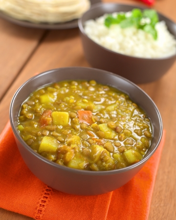 Bowl of spicy Indian dal (lentil) curry prepared with carrot and potato, rice and chapati flatbread in the back (Selective Focus, Focus one third into the curry) Stock Photo