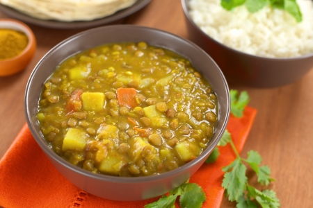 Bowl of spicy Indian dal (lentil) curry prepared with carrot and potato, rice and curry powder in the back and cilantro leaf on the side photo
