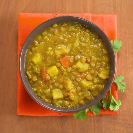 lentilha: Bowl of picante dal indiana (lentilha) caril preparado com cenoura e batata, com folha de coentro no lado