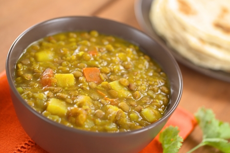 curry dish: Bowl of spicy Indian dal (lentil) curry prepared with carrot and potato, chapati flatbread in the back and cilantro leaf on the side Stock Photo