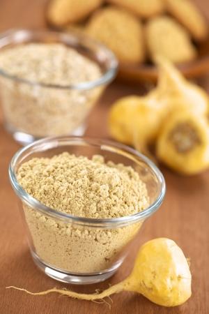 Maca en poudre (farine) dans un bol en verre avec racines de maca ou ginseng péruvien (lat. Lepidium meyenii) et d'autres produits péruviens de maca (flocons d'avoine avec la maca maca et les cookies) à l'arrière (sélective Focus, Focus tiers dans la poudre de maca et sur la avant de l'