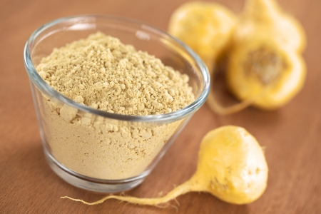 Maca powder (flour) in glass bowl with maca roots or Peruvian ginseng (lat. Lepidium meyenii) (Selective Focus, Focus one third into the maca powder)