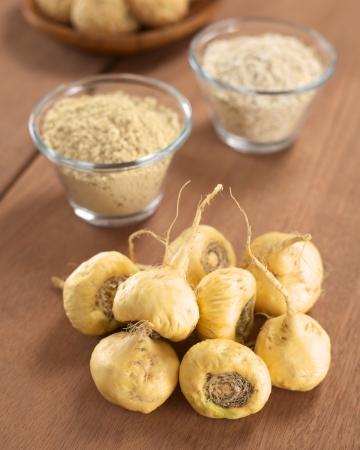 Verse maca wortels of Peruviaanse ginseng (lat. Lepidium meyenii), die populair zijn in Peru voor hun verschillende effecten op de gezondheid met maca producten (maca poeder, havermout met maca, maca cookies) in de rug (selectieve aandacht, Focus op de maca wortels in de front)