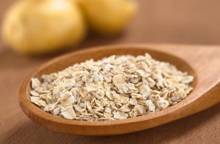 maca: Harina de avena mezclada con polvo de maca o ginseng peruano (lat. Lepidium meyenii) en la cuchara de madera con ra�ces frescas de maca en la parte posterior (foco selectivo, foco tercera en la avena)
